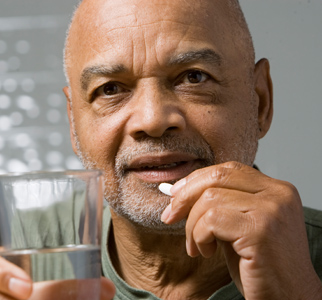 Older man with pill and glass of water